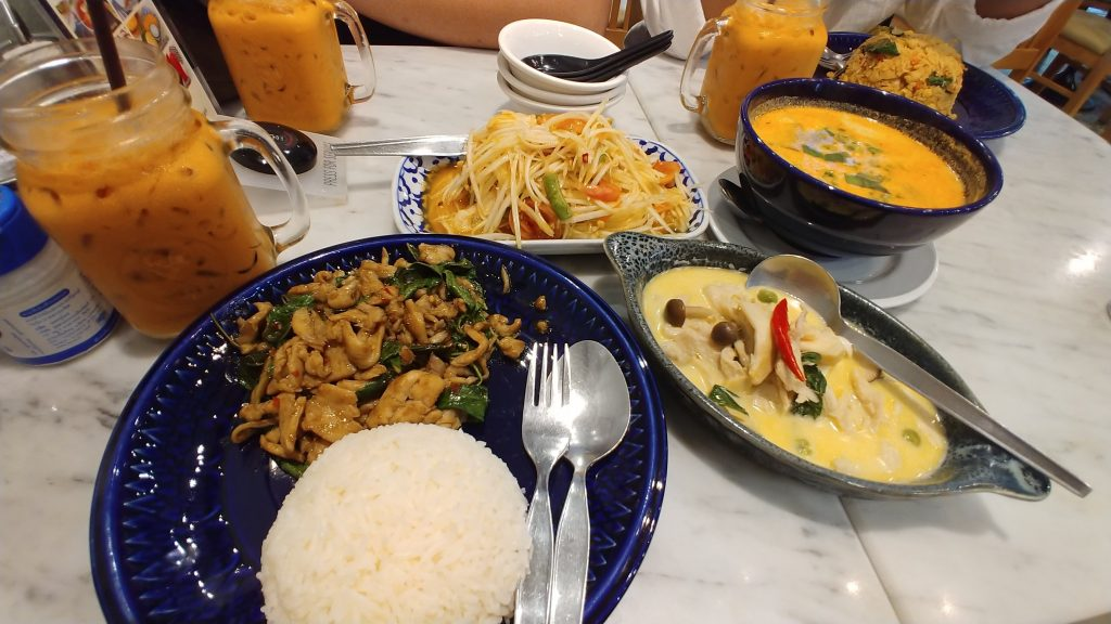 Chicken Basil with Rice (Pad Kra Pao Gai, Papaya Salad (Som Tum), Tom Yum, Green Curry (Gaeng Keow Waan), Tom Yum Fried Rice, dan segelas Thai Tea